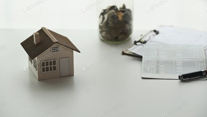 Coins stack with house model, paper house and business document chart on white desk.