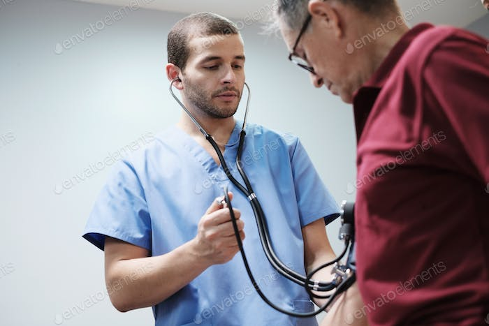 Nurse and Doctor Measure Hispanic Old Man Blood Pressure