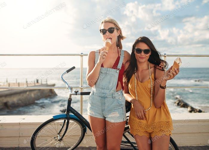 Weibliche Freunde mit einem Fahrrad essen Eis