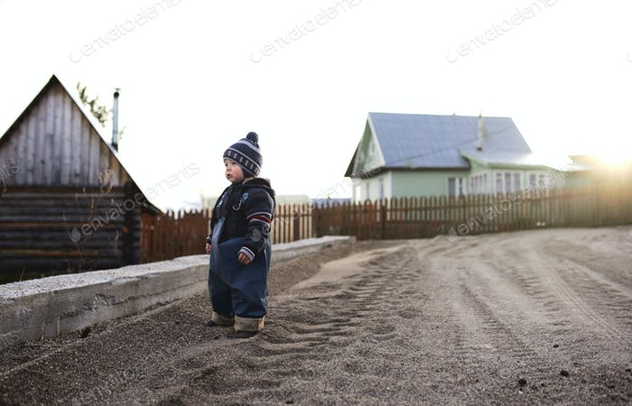 A boy in the village walks on the sand and plays with stones.