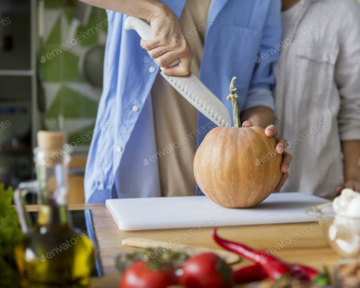 Man cutting small pumpkin for pie in the kitchen