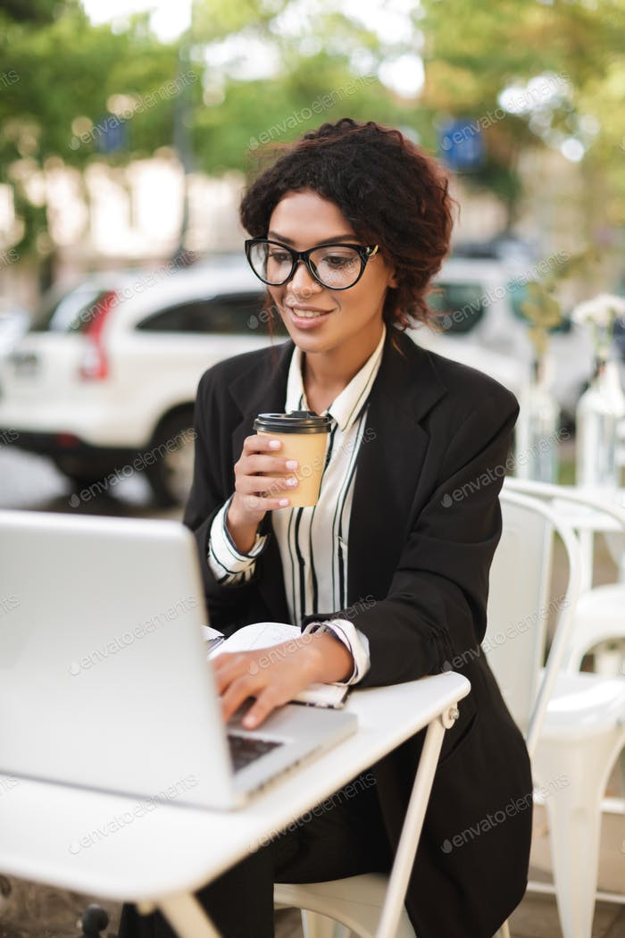Smiling African American girl in glasses sitting at the table of cafe and working on her laptop