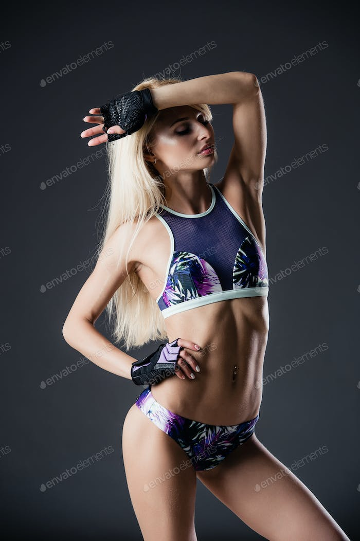 Portrait of sexy young woman with her hands on hips looking at camera. Fitness female with muscular