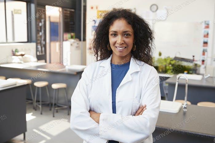 Profesora Mujer en bata de laboratorio sonriendo en sala de Ciencia escuela