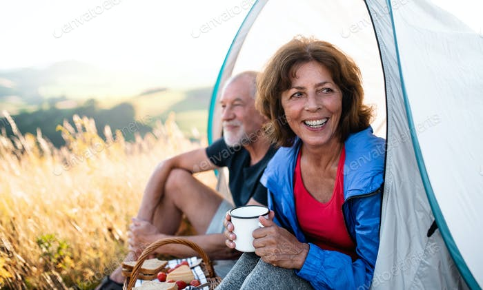 Senior tourist couple with picnic basket sitting in nature at sunset, resting.