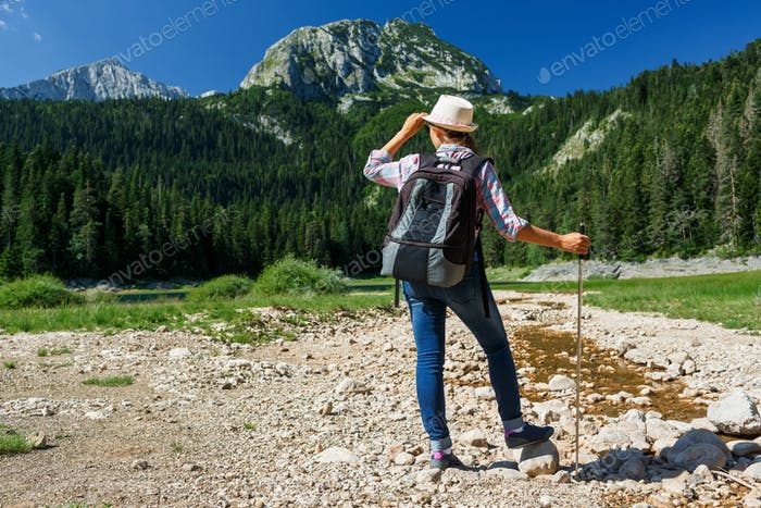 Woman hiker with a backpack and walking stick on the Black Lake