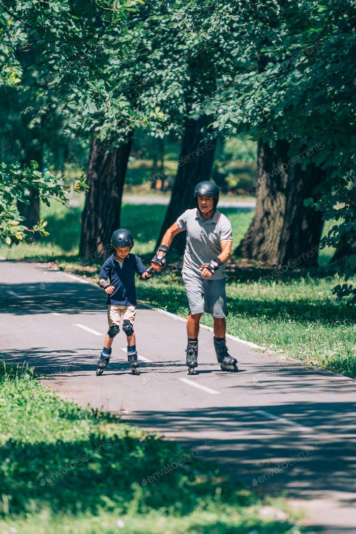 Grandfather and grandson enjoying roller skating