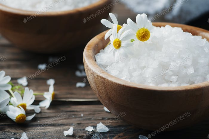 Concept of spa treatment with salt and daisy