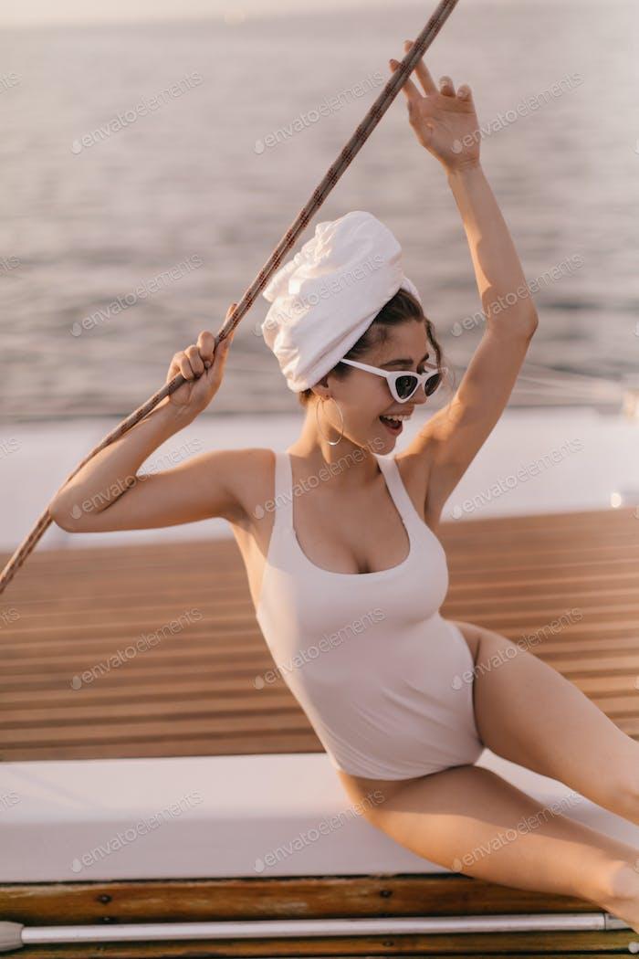 Aufgeregte junge Dame im weißen Badeanzug, handtuchgehendes Haar, stilvolle Sonnenbrille und Ohrringe, sitzend