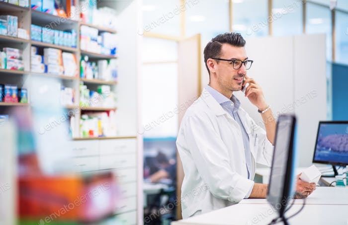 Young friendly male pharmacist with smartphone, making a phone call.