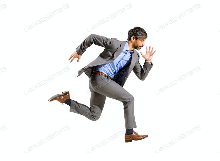 Elegante empresario corriendo a gran velocidad en una zancada aérea
