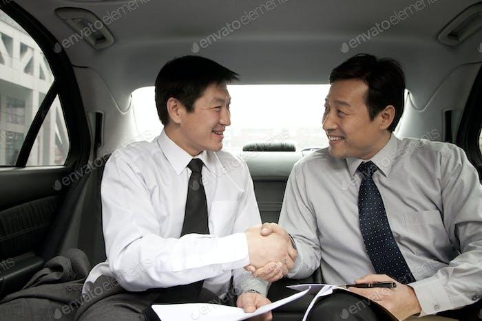 Zwei Geschäftsleute schütteln die Hände in einem Auto
