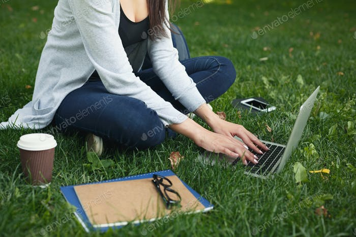 Young pensive woman using laptop in park