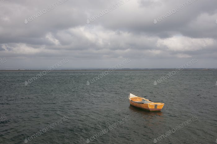 A small wooden boat moored in open water, off the Portuguese coast.