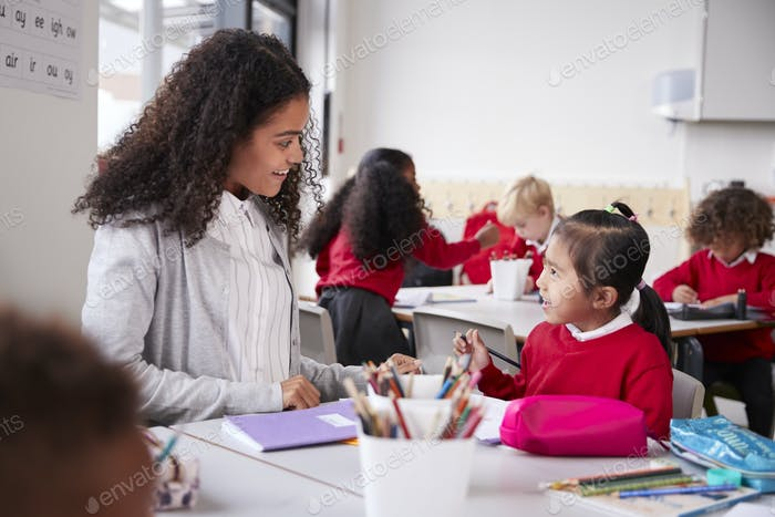 Female kindergarten teacher sitting at table in a classroom talking to a young Chinese schoolgirl