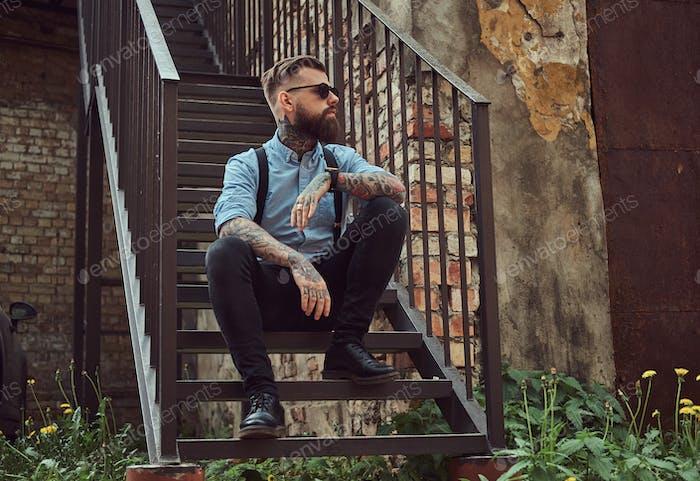 Стильный красивый старомодный татуированный хипстер парень в рубашке с подтяжками, сидящий на лестнице