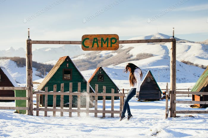woman play with snow at ski resort camp