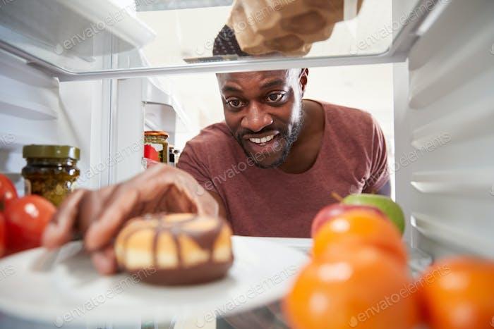 Blick aus dem Inneren des Kühlschranks als Mann öffnet Tür und reicht für ungesunde Donut
