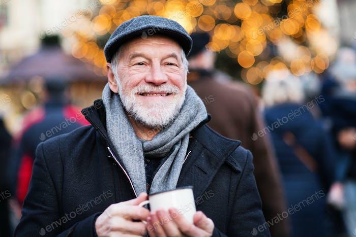 Senior man on an outdoor Christmas market.