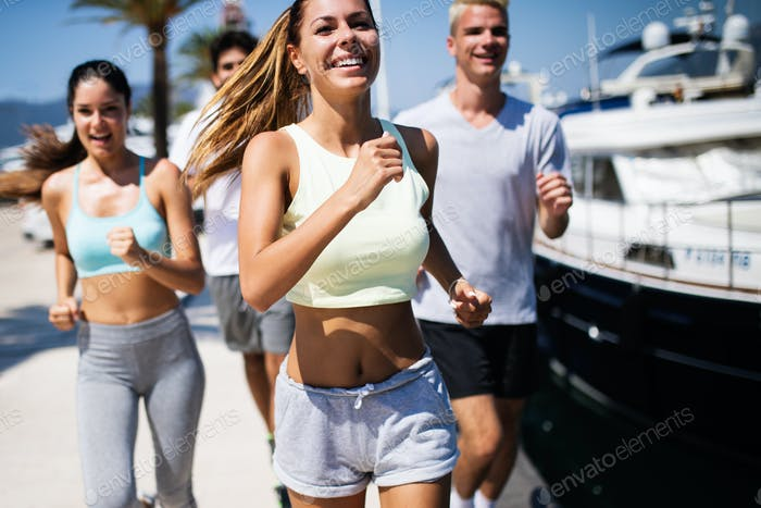 Running, friends, sport, exercising and healthy lifestyle concept. Happy people jogging outdoor