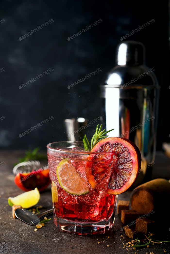 Blood Orange Margarita coctail with ice and thyme on dark backgorund