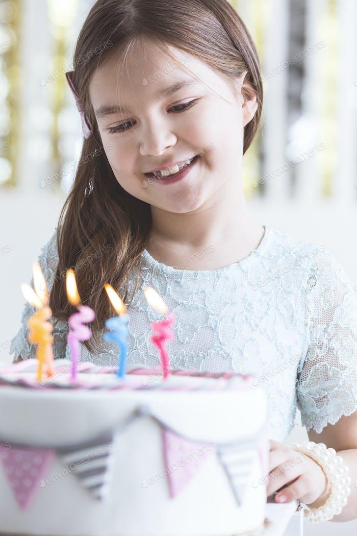 Kleines Mädchen mit Geburtstagskuchen
