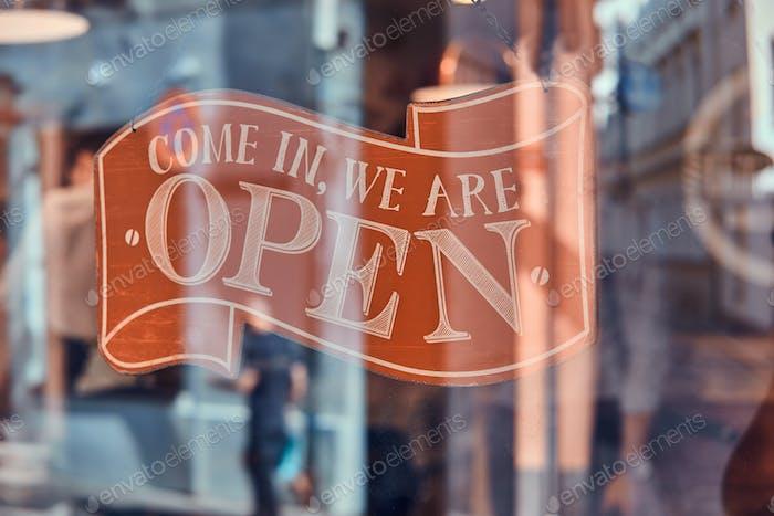 Schönes Typenschild mit Informationen über das Öffnen unter dem Glas bei Barbershop
