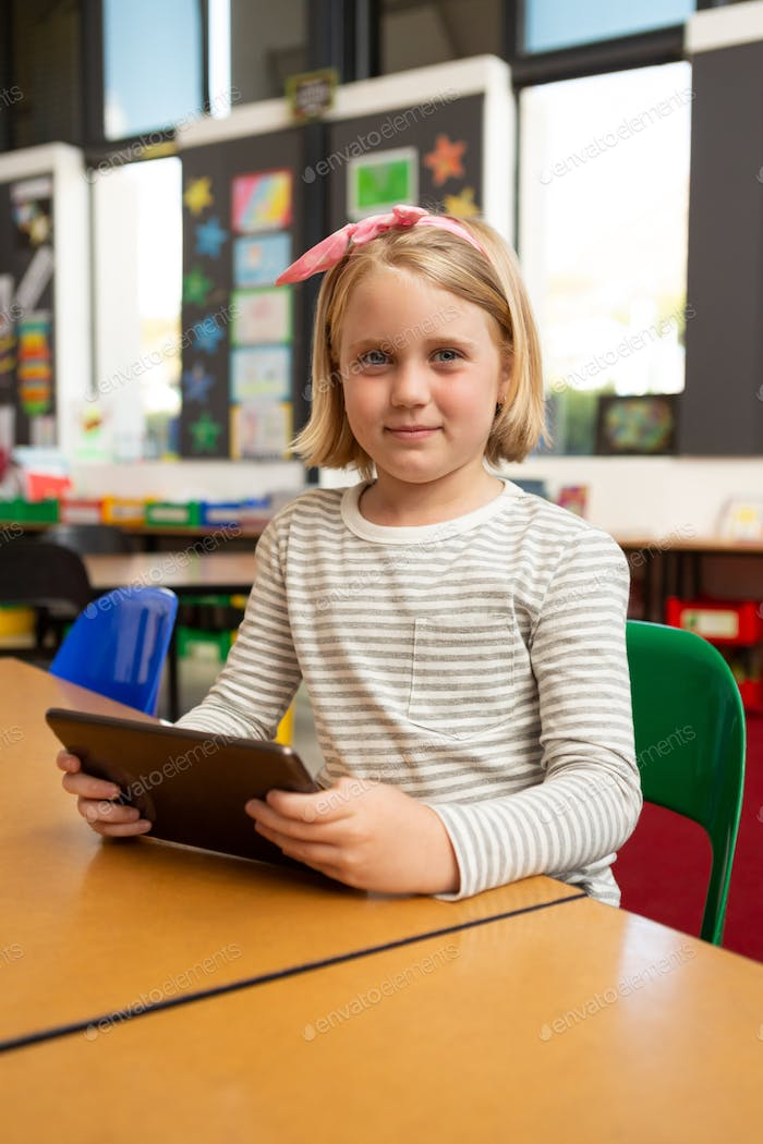 Schoolgirl using digital tablet while looking at the camera in the classroom at school