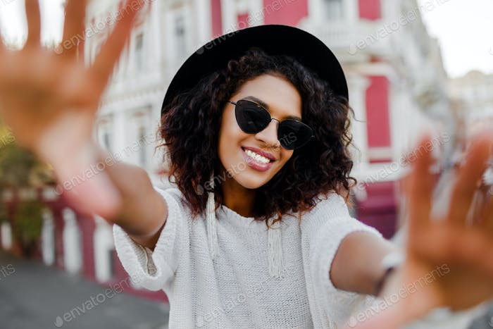 woman with stylish Afro hairs making self portrait.