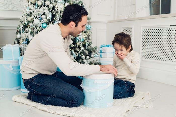 Lächelnder Vater und sein Sohn öffnen Weihnachtsgeschenke im Wohnzimmer