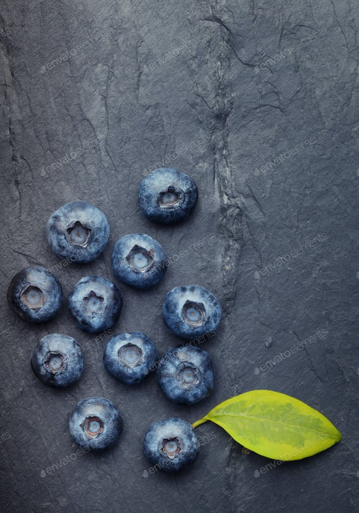 A bunch of delicious blueberries with green leaf on a  black vin
