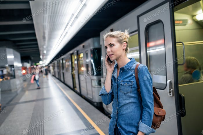 Woman making phone call at the underground platform