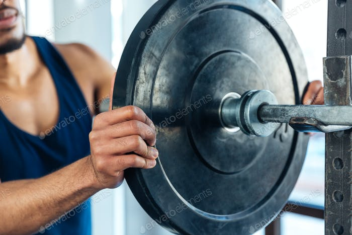 Healthy fitness guy prepare to do exercises with barbell