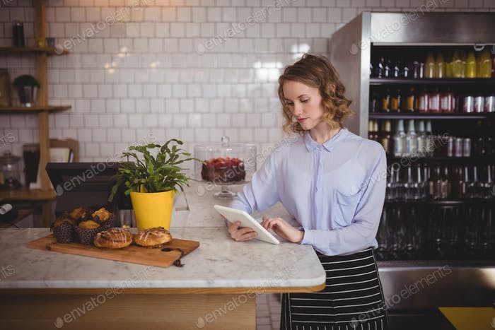 Attractive young waitress using digital tablet while standing by counter