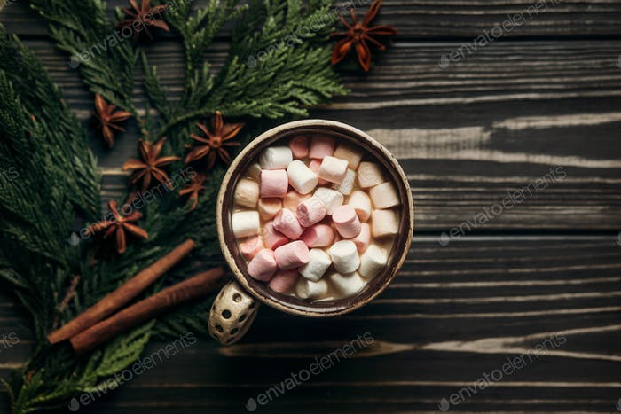 Rustic winter flat lay of chocolate cocoa cup with colorful marshmallows