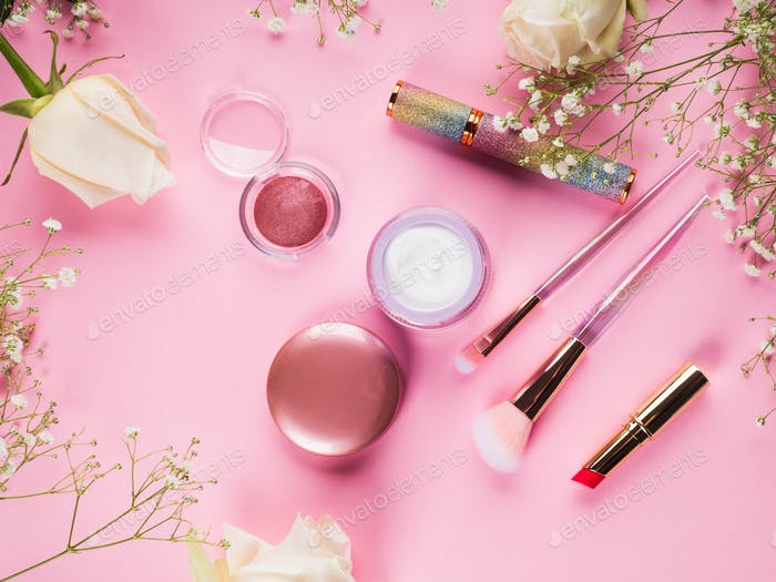 Shiny make up products and accessories on pink