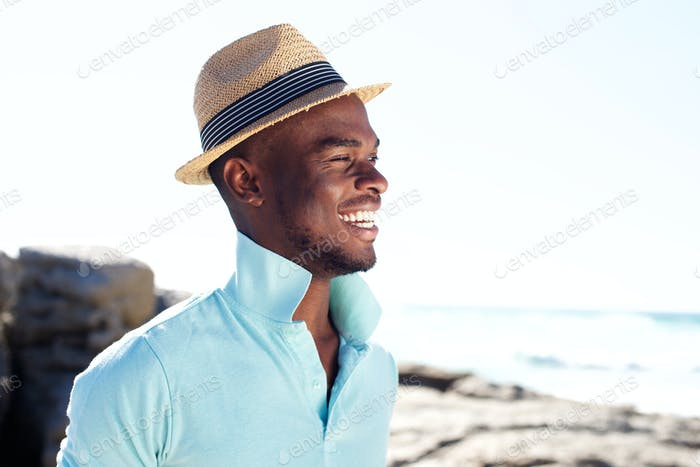 Handsome young guy smiling at the beach