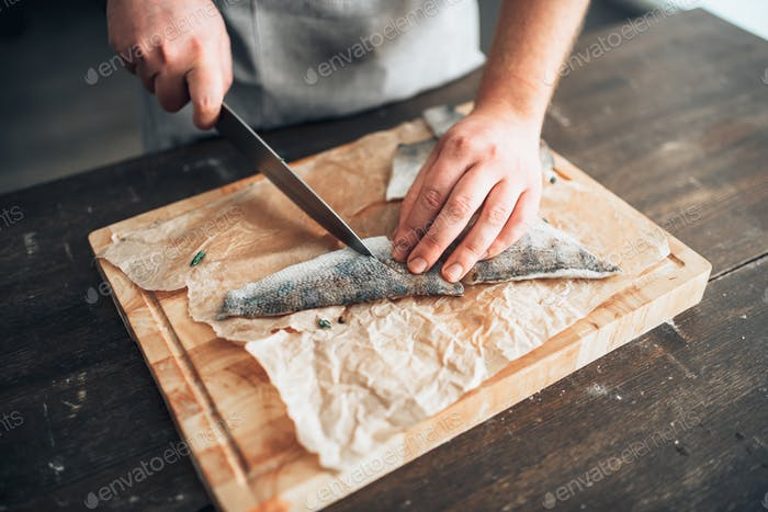 Chef cuts raw fish slices on wooden cutting board