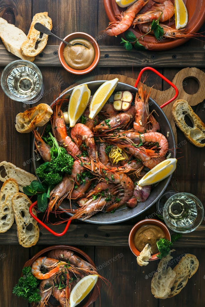 Huge prawns in a pan with bread, sauce and wine