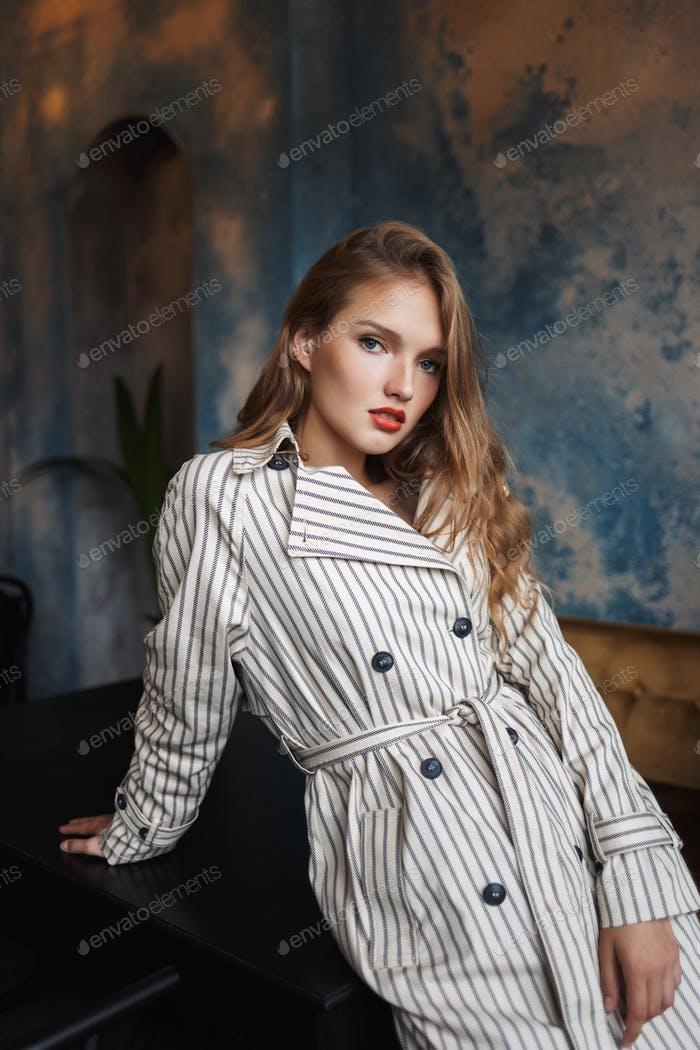 Young pensive woman with wavy hair in striped trench coat leanin