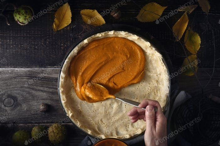 Putting  pumpkin puree on the dough for pumpkin pie on the wooden table