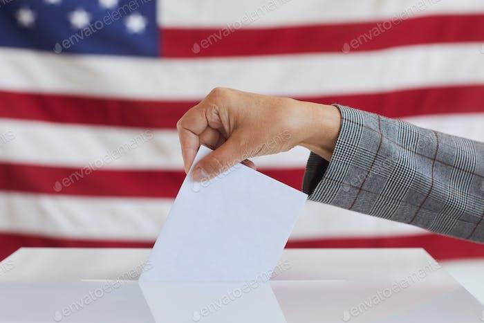 Mano femenina poniendo voto en las urnas