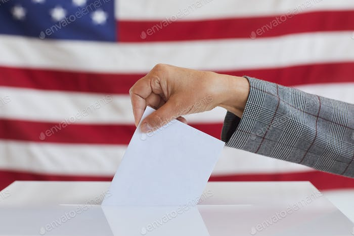 Female Hand Putting Vote in Ballot Box