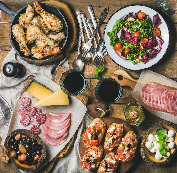 Thumbnail for Rustic table set with salad, chicken, brushettas, olives, red wine