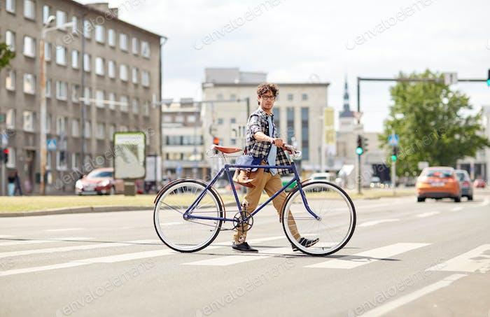 junger Mann mit festem Getriebe Fahrrad auf Fußgängerübergang