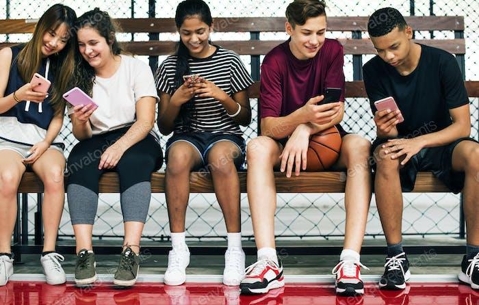 Gruppe von jungen Teenager-Freunden auf einem Basketballplatz entspannen mit Smartphone