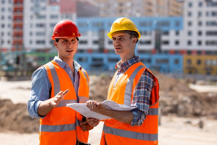 Two men dressed in shirts, orange work vests and helmets discuss documentation on the building site