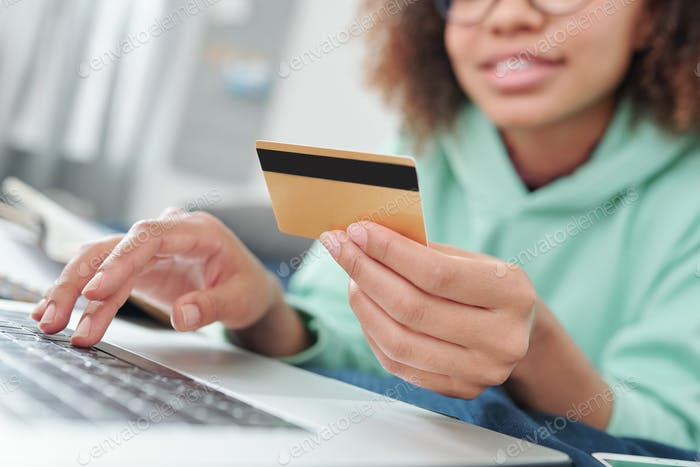 Hands of young contemporary female with credit card over laptop keypad