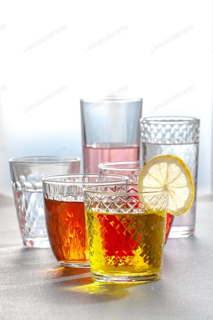 Verschiedene Limonaden in Glasfacettierten Gläsern auf einem grauen Tisch. Phot