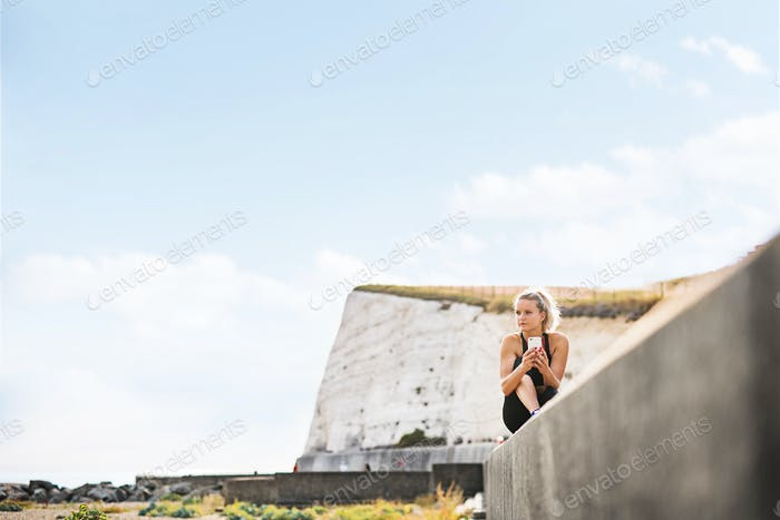 Young sporty woman runner with smartphone sitting on the beach outside, texting.